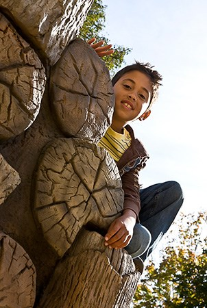 A boy smiling at camera while leaning over a  log stack climber with wood grain hand holds.