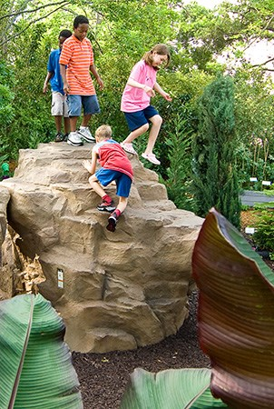 A group of children climbing on a Pinnacle rock climber surrounded by a garden.