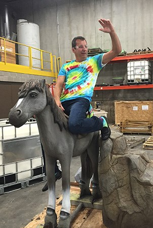 Landscape Structures President Pat Faust pretends to ride a fiber glass reinforced pony concrete statue.