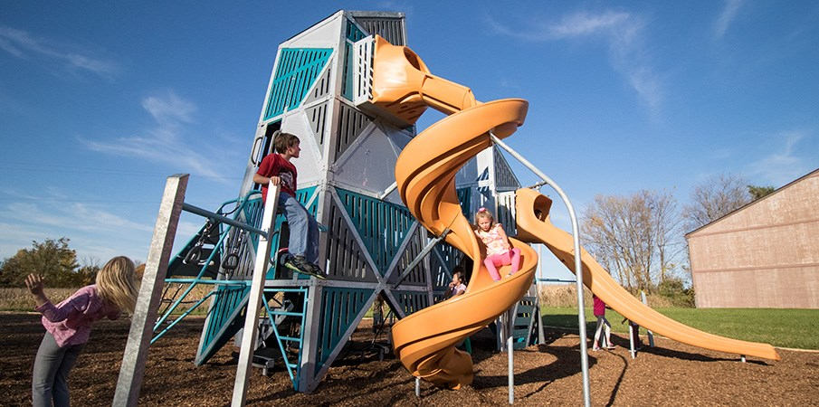 Children playing on the Alpha Link Towers, using the two slides to navigate from the deck to the ground.