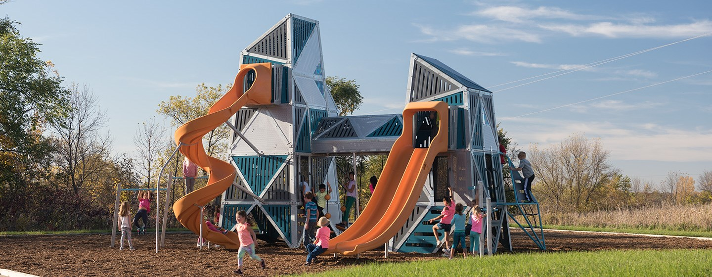 Double climbing towers with a connected crawl tunnel shows with kids climbing and sliding down the curved open bedway slide and a double bedway slide of different heights.