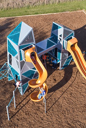 Top down view of the two towers that comprise the Alpha Link Towers playstructure. A spiral WhooshWinder slide in tangerine compliment the lagoon and gray features of the climbing towers and added play events. A tangerine polyethylene Double Swoosh slide is also shown.