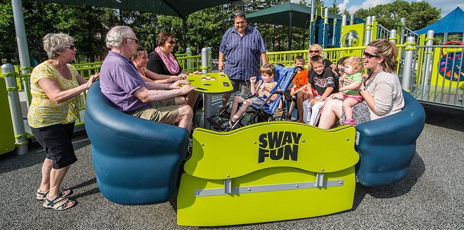 Adults and children all playing on a inclusive Sway Fun glider.