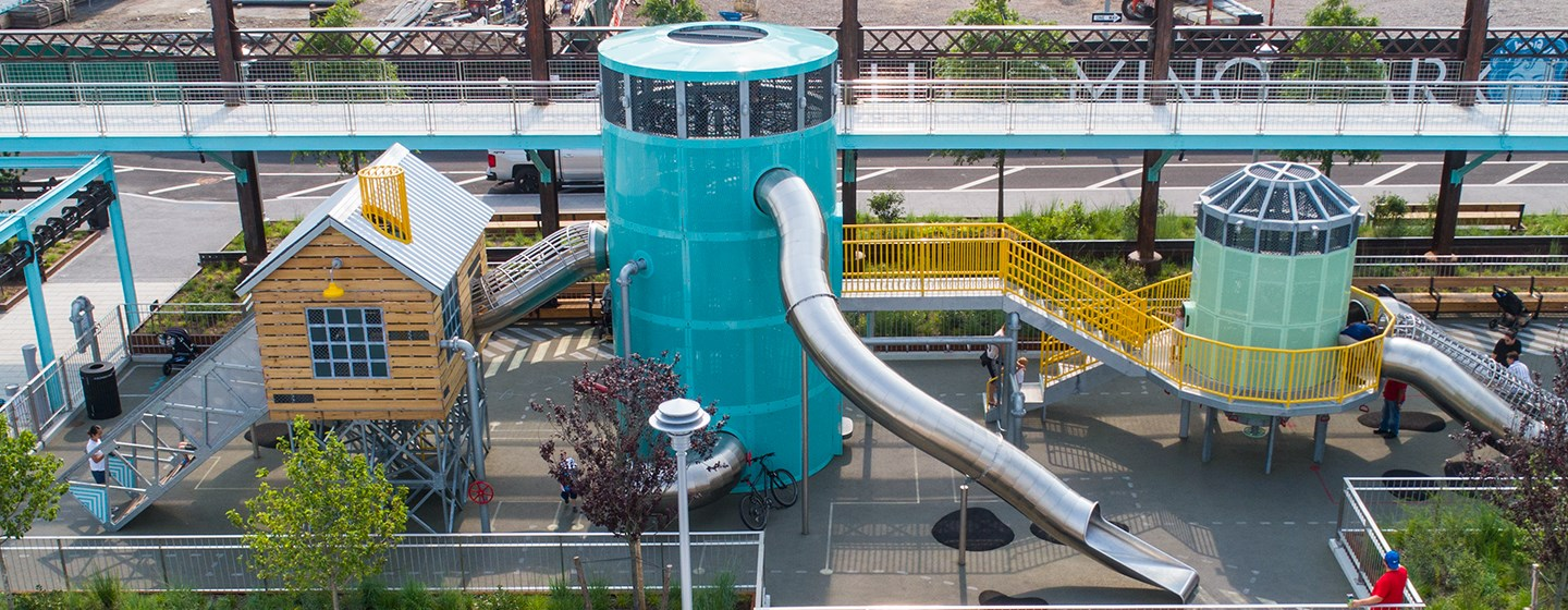 Elevated side view of the three playground structures of the Sugar Factory themed playground at Domino Park in Brooklyn New York.