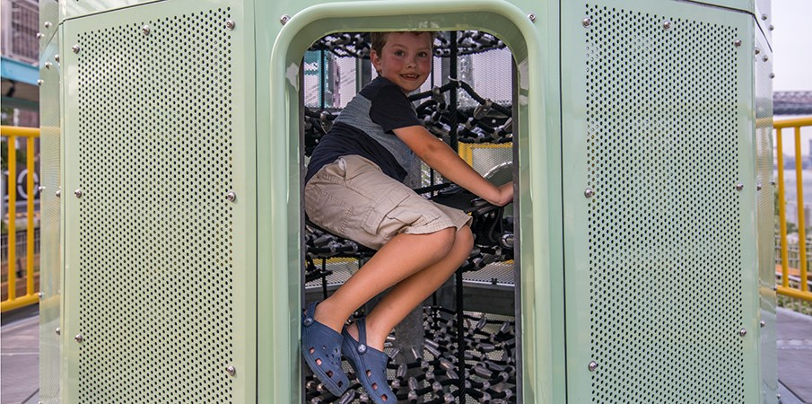A young boy climbing inside the Centrifuge playground structure cargo net climber.