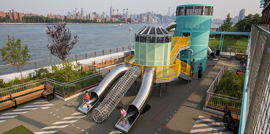 Two children running out of the stainless-steel slides of the Centrifuge playground structure at Domino Park.