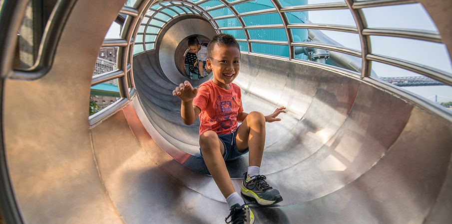 A boy sliding towards camera from the stainless-steel crawl tunnel on a sugar mill themed playground
