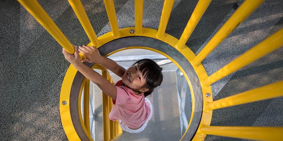 A young girl smiles up at the camera while climbing up into the sugar mill themed play structure on a vertical ladder.