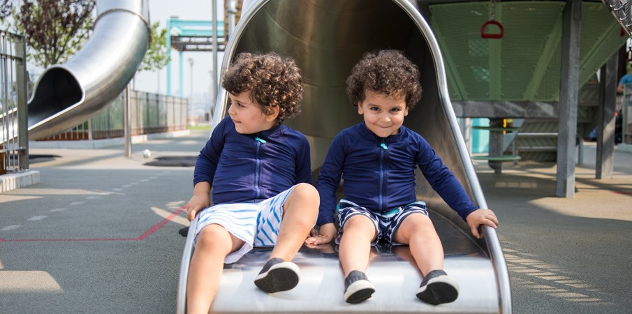 Young twin boys sit at the bottom of a stainless-steel slide off of the Centrifuge playground structure at Domino Park.