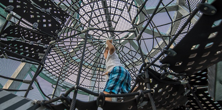 A boy runs on unique belted cargo net climbing inside the Sweetwater Silo playground structure at Domino Park.