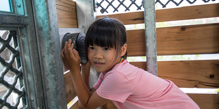 Young girl holds her ear to a talk tube in the Sugar Cane Cabin at Domino Park.