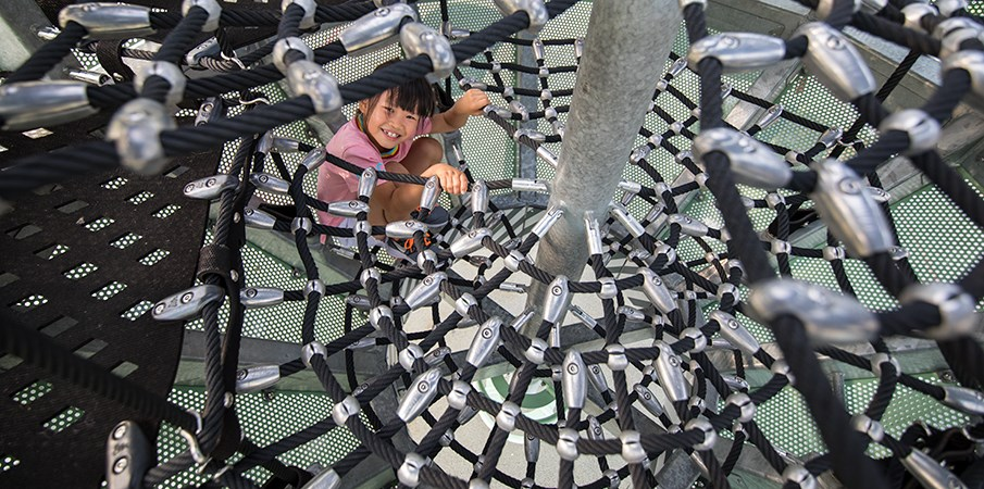 Young girl looks up and smiles at camera while climbing through the Sweetwater Silo cargo net climber.