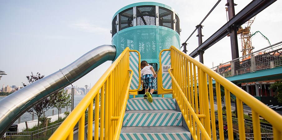 A boy runs up the some playground steps to the Sweetwater Silo playground structure at Domino Park.