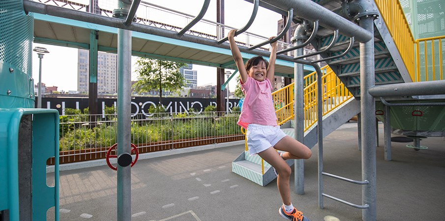 Young girl smiles as she swings on playground monkey bars at Domino Park.
