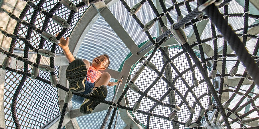 Young boy looks down through cargo net climber as he smiles at camera in the Sweetwater Silo at Domino Park.