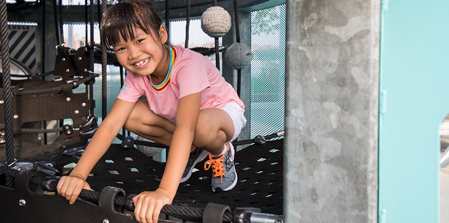 Young girl smiles at camera from inside the Sweetwater Silo structure while kneeling on belted net climber.