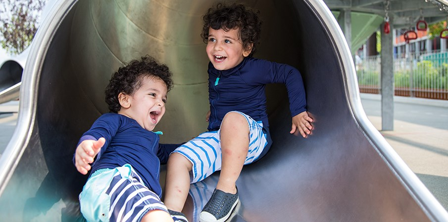 Young twin boys smile as they slide down a stainless-steal playground slide at Domino Park.