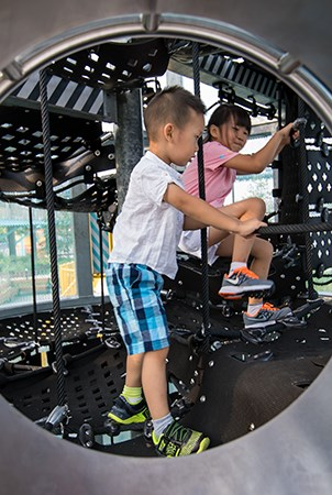 A boy and girl play inside the Sweetwater Silo playground structure on the belted cargo net climber.