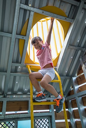A young girl climbing on a vertical ladder up to a chimney cage roof top viewer in the Sugar Cane Cabin at Domino Park.