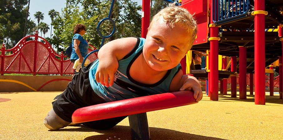 Young boy smiles at the camera as he lays across a pod climber at an inclusive playground.