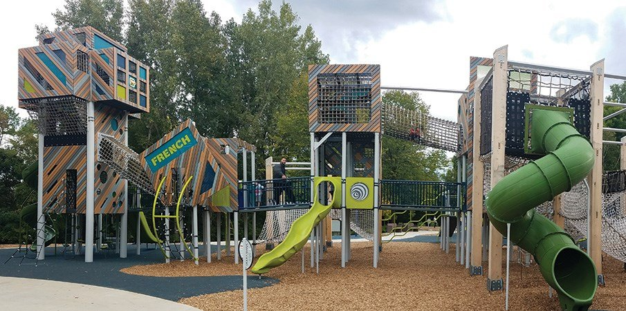 Ground level view of the unique playground with connecting tower and cargo net climbers.