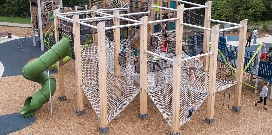 Elevated view of children climbing on the large cargo net playing area at the French Regional Park playground.