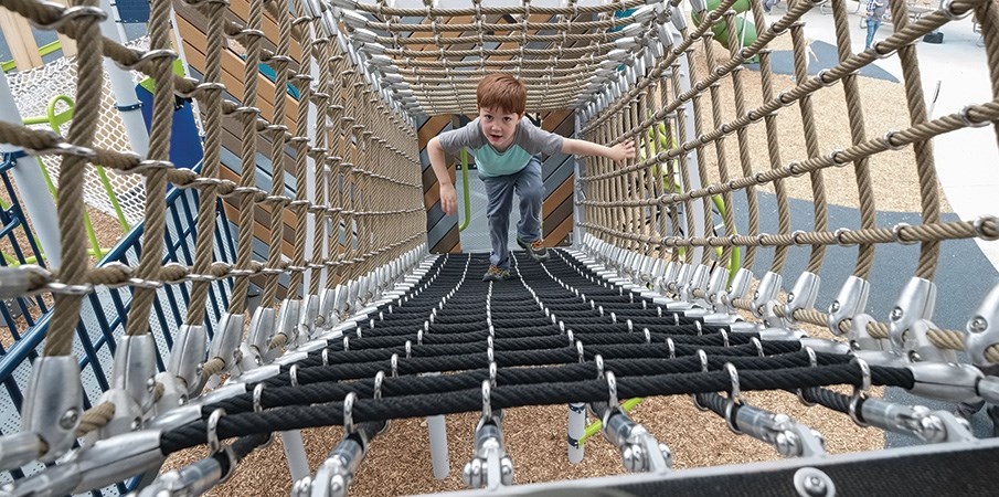 A boy climbing up a square playground cargo net tunnel.