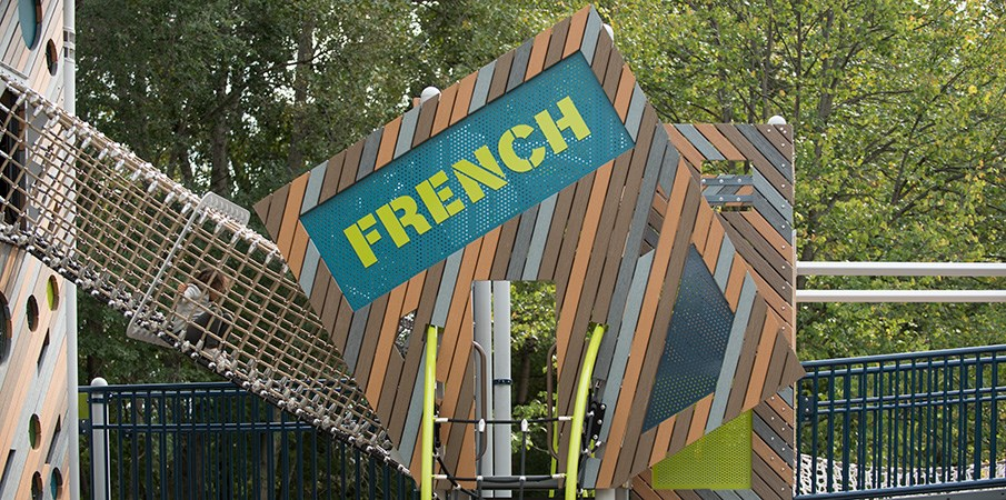 A cargo net tunnel connecting two play structures made of a mix of real and recycled plastic lumber with a sign reading French.