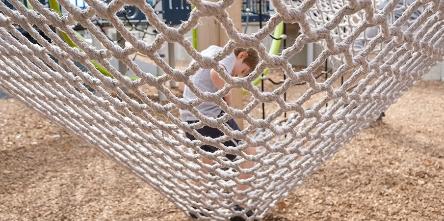 View of a boy through a playground cargo net as he stands.
