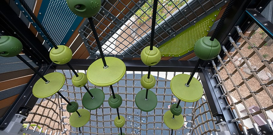 Top down view of a elevated SwiggleKnots bridge inside a playground tower.