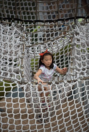 A girl climbing out of a cargo net maze at French Regional Park.