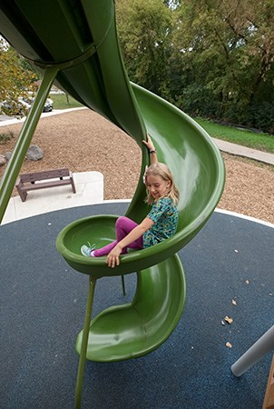 Top down view of a girl sliding down the first turn of the WhooshWinder slide.