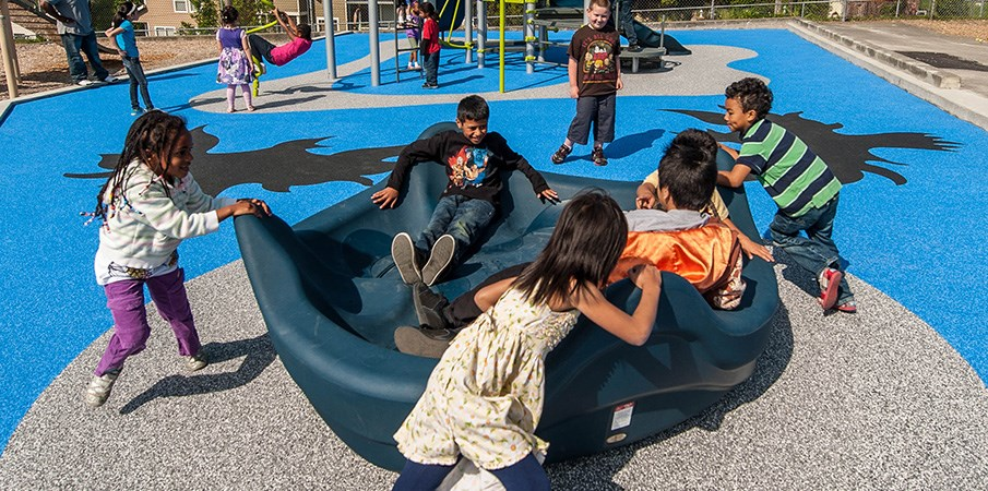Children play on a inclusive OmniSpin playground spinner.