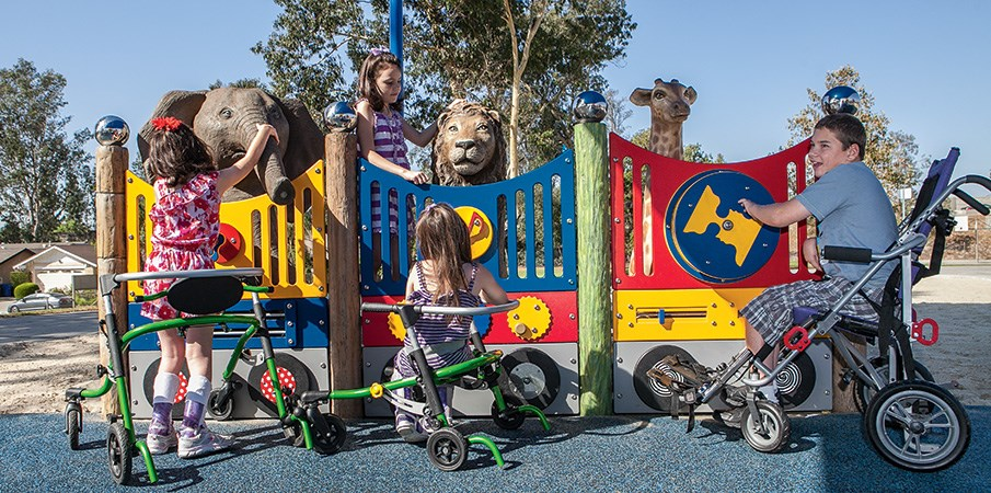 Three children play at sensory reach panels at an inclusive zoo themed playground.
