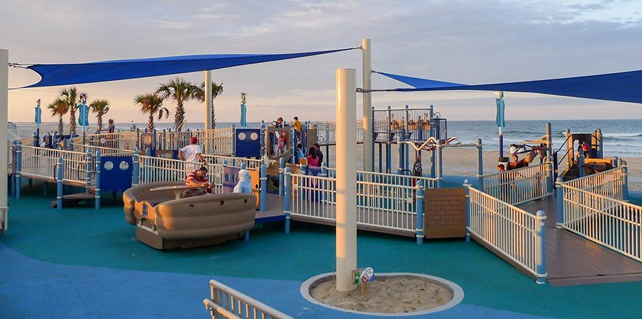 A inclusive playground set next to a ocean beach.