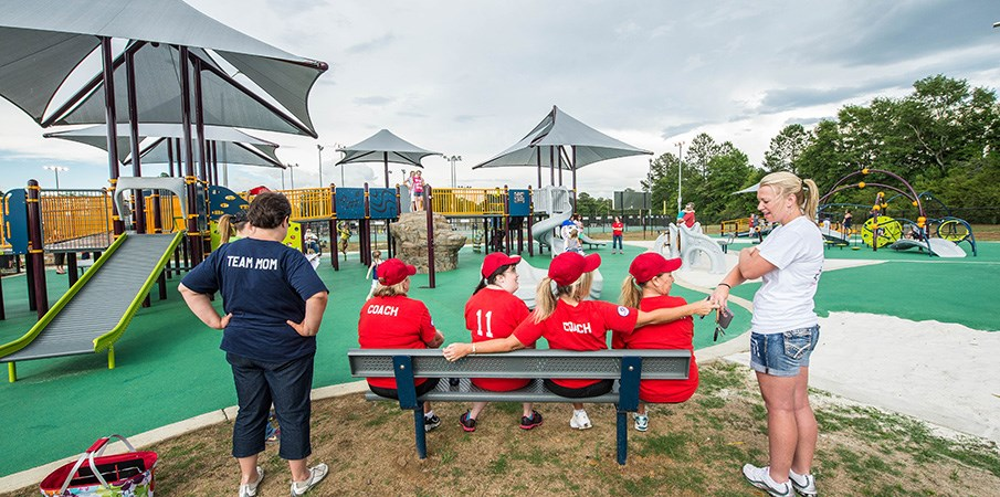 Players and coaches sitting on a bench at a inclusive playground.