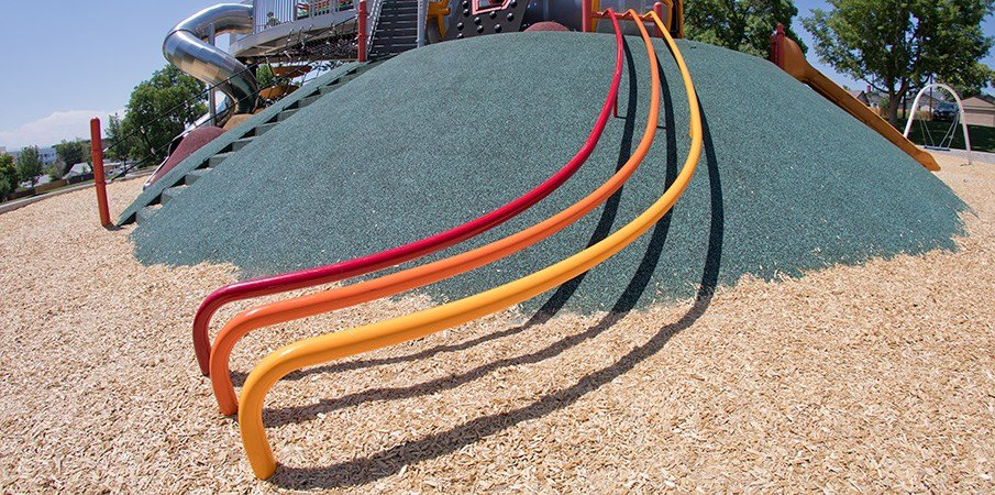 A ribbon slide running down the side of a small PebbleFlex covered hill.