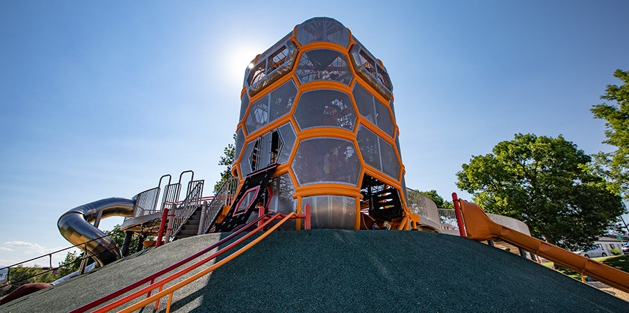 The main playground structure sitting at the top of a PebbleFlex surfaced hill with climbers and slides leading up to it.