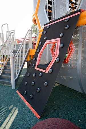 Belted playground climber with foot and hand handholds.