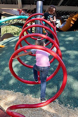 Two girls climb on the horizontal metal spiral playground climber.