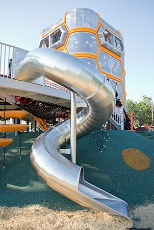 A stainless steel tubular spiral playground slide.