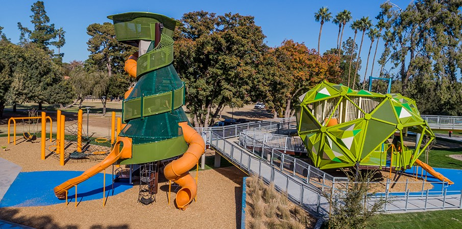 Full view of Pioneer Park, playground structures designed to look like a pine tree, a palm tree, and a pistache tree.