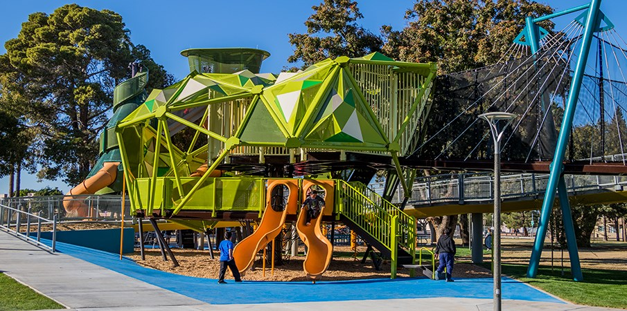 Ground level view of the pistache tree playground structure with SlideWinder and a Rushwinder slides.