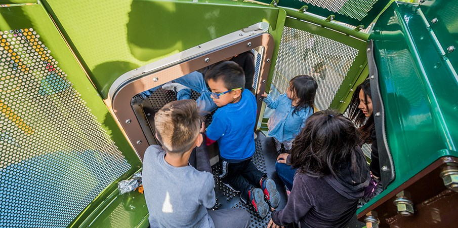 Top down view of children kneeling inside the top of the pine tree playground structure.