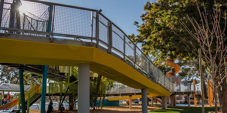 Ground level view of the ADA wheelchair elevated ramp leading to the playground structures.