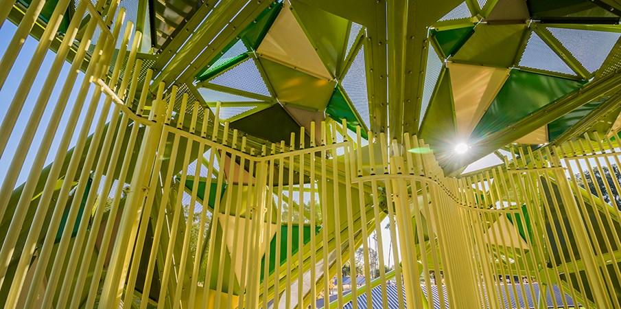 Sun beaming in through the geometrical shaped roof panels of the pistache tree playground structure.