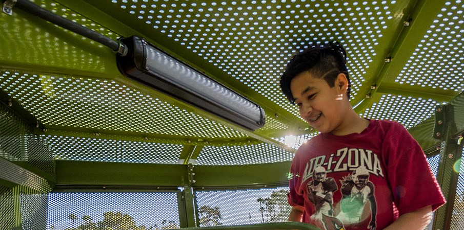 A boy smiles while standing in the top of the palm tree playground structure.