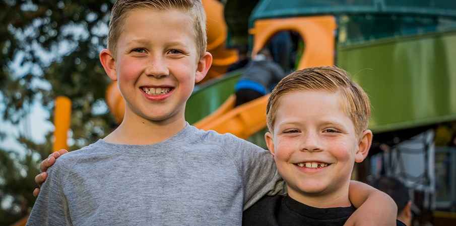 Two boys standing side by side smiling at the camera in front of the playground.