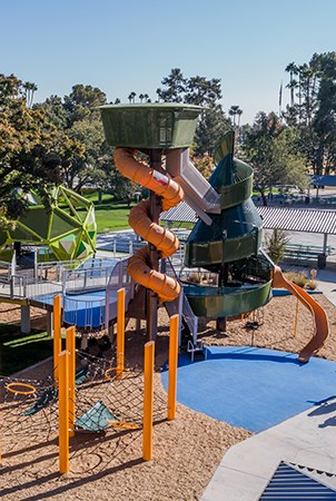 Elevated view of the palm tree and pine tree playground structures with slides and cargo net climber.
