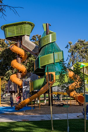 Ground level view of the palm tree and pine tree playground structures with slides.